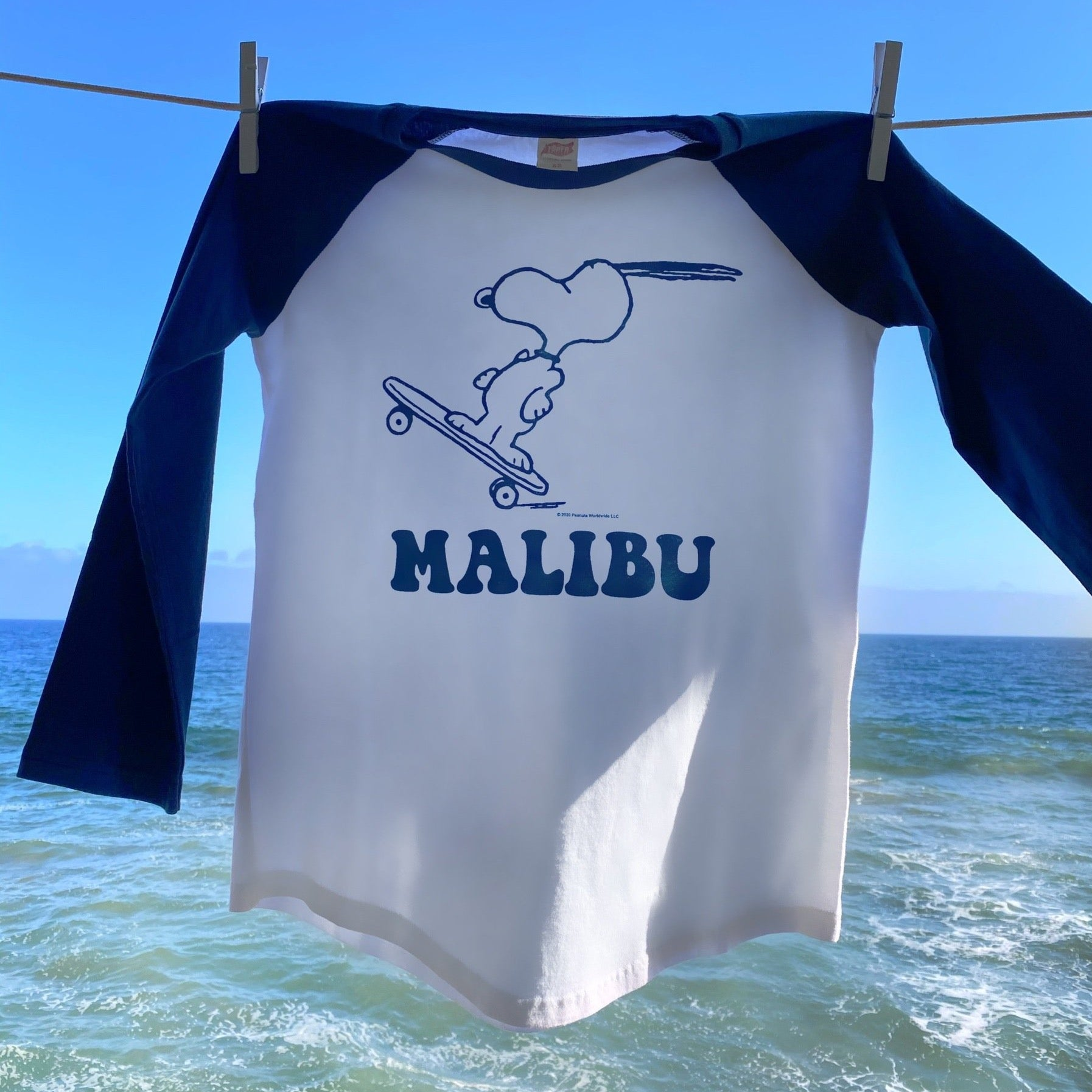 TSPTR Malibu Peanuts Raglan T-Shirt. White shirt with blue sleeves. Design of Snoopy riding a skateboard on the front.