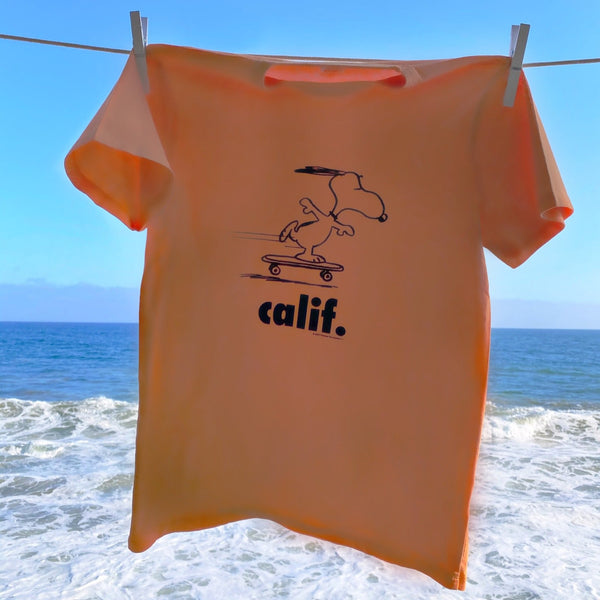 Orange Peanuts Calif T-Shirt with a design of snoopy skateboarding.