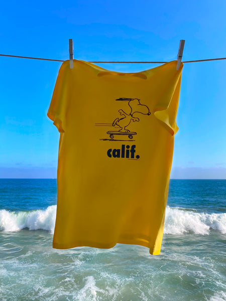Yellow  Peanuts Calif T-Shirt with a design of snoopy skateboarding.