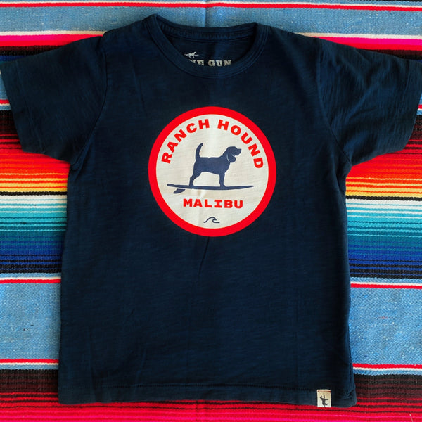 One Gun Ranch Hound Malibu Kids T-Shirt. 100% cotton. Made in Los Angeles. Blue shirt with a red white and blue design in the center.