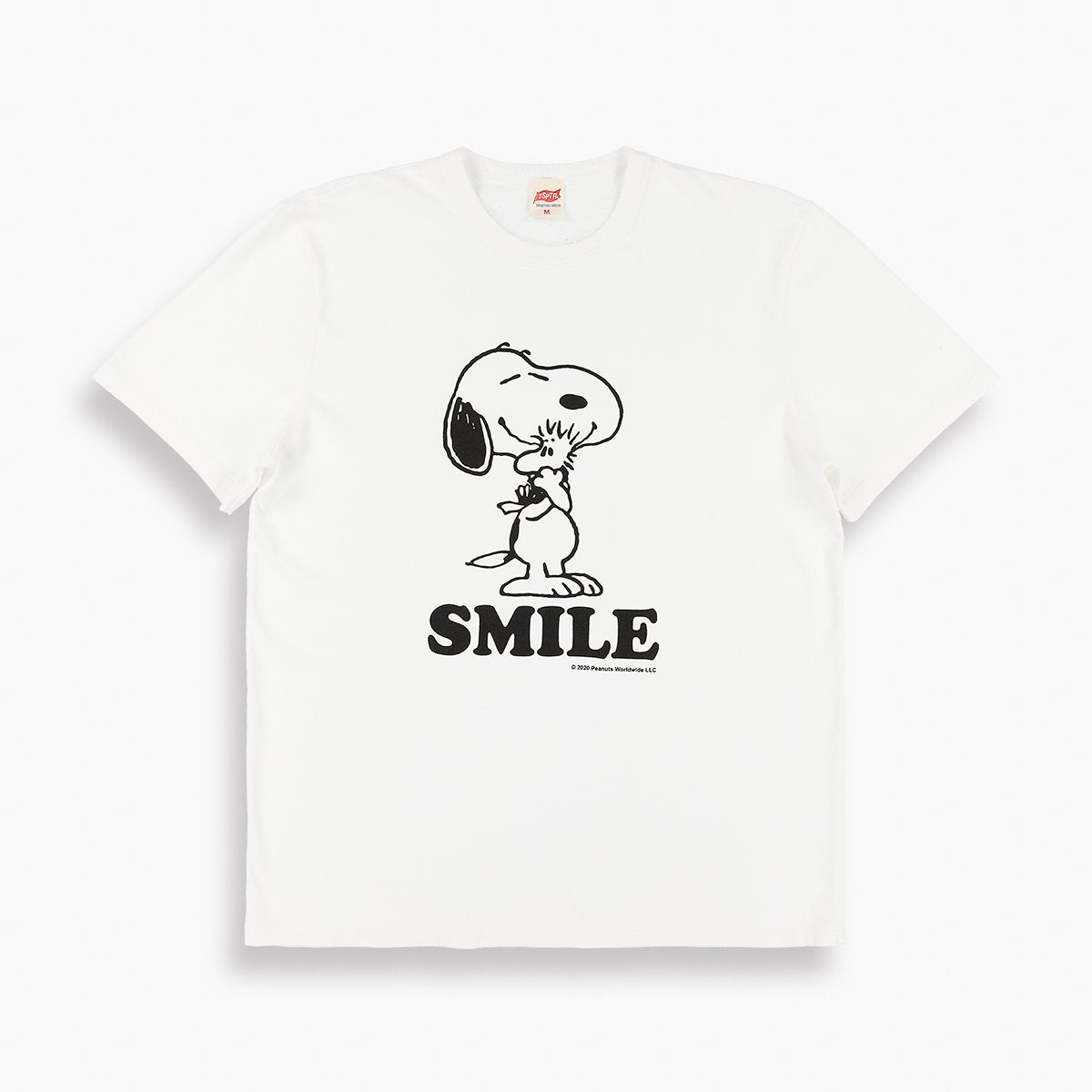 White shirt with a design of Snoopy hugging Woodstock. The word SMILE in black text at the bottom.