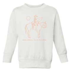Kids white sweatshirt with a pink outline drawing of a woman riding a horse and holding a surfboard. Underneath the text reads gracias california X one gun ranch malibu