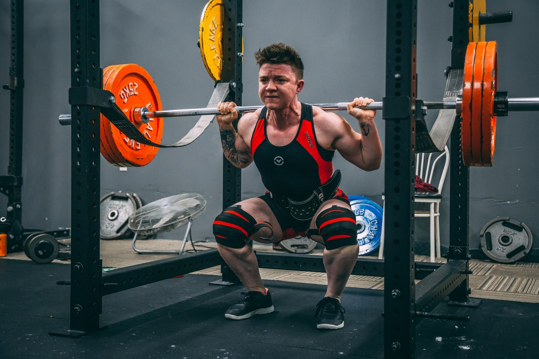 man wearing a black and red vest doing back squats in a gym