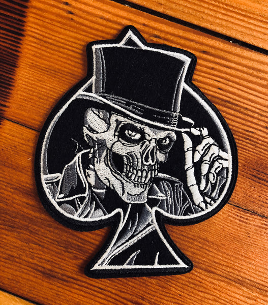 Skull in a top hat popping out of a spade