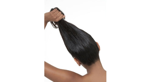 black woman holding hair up and showing crown and back of edges and hair line