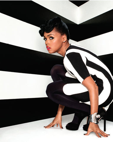 Image of Janelle Monae in black and white trendy outfit crouching to the floor