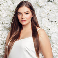 Plus size model in white in front of white flower wall