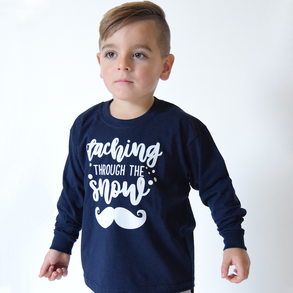 Young boy wearing navy shirt with long sleeves with 'Staching through the snow' print by KMLeon.