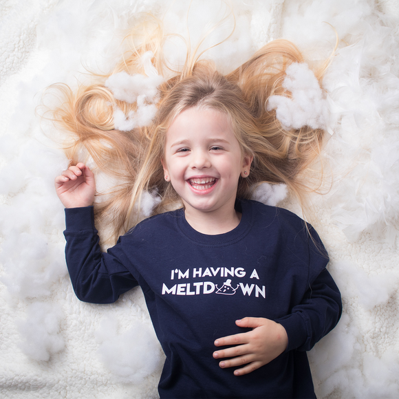 Laughing blonde girl laying on snow with hair spread out, wearing navy shirt with 'I'm having a meltdown' print by KMLeon.