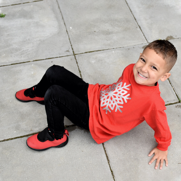 Boy with red shoes and red shirt with long sleeves with glitter snow star print sitting on concrete floor.