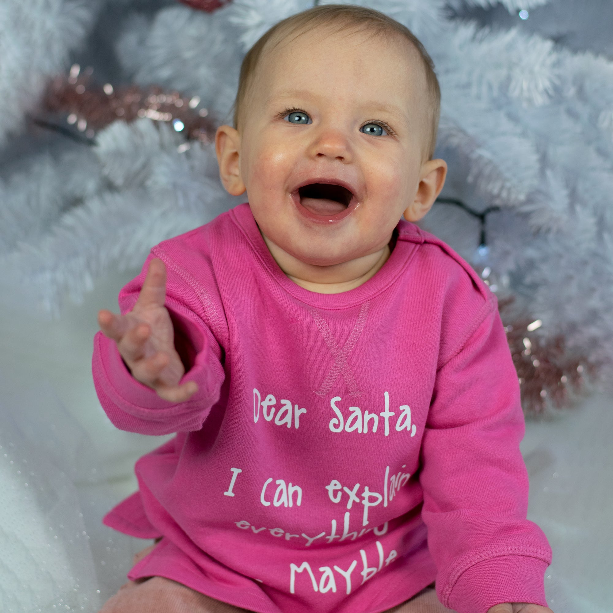 Baby girl with blue eyes and pink sweater with 'Santa, I can explain everything' sweater by KMLeon.