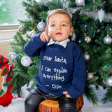 Boy with Navy sweater with 'Santa, I can explain everything' print by KMLeon in front of christmas tree, pointing his finger.