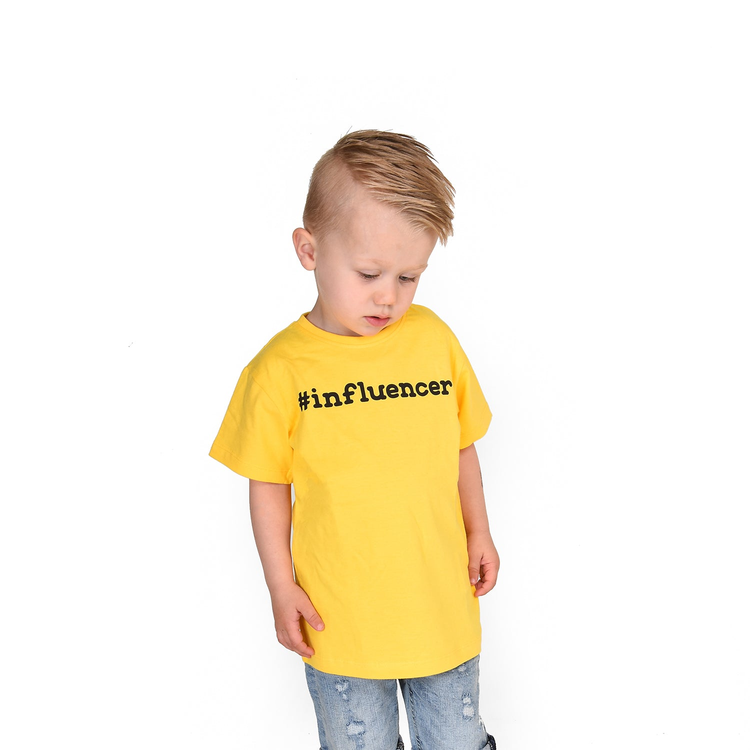 Blonde boy looking at his feet with yellow shirt, with '#influencer' print, by KMLeon.