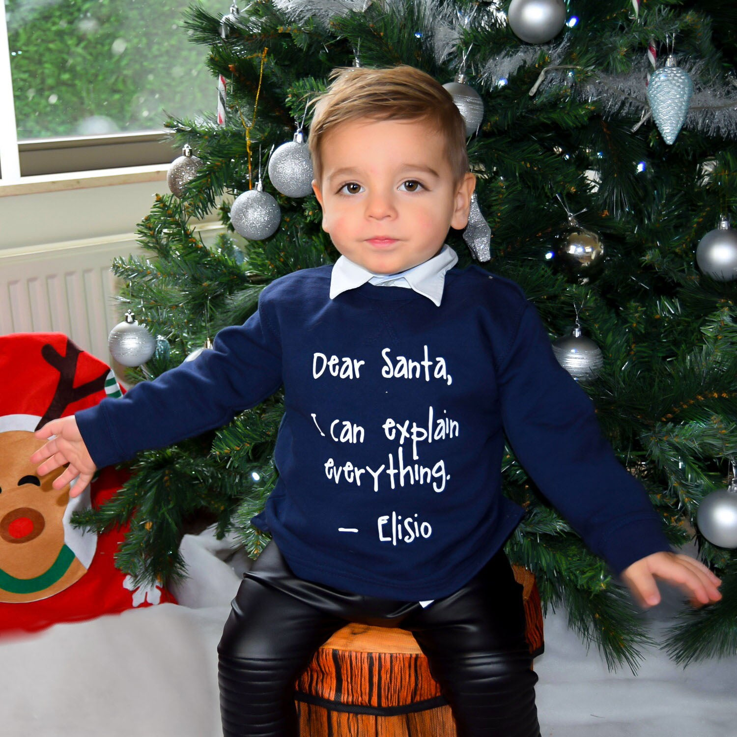 Boy with Navy sweater with 'Santa, I can explain everything' print by KMLeon in front of christmas tree.