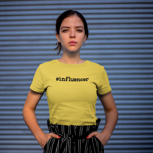 Serious women with yellow shirt with '#influencer' shirt by KMLeon against blue background.