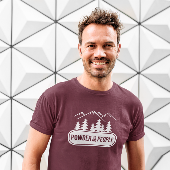 Smiling man in front ogf white graphic wall, wearing burgundy shirt with 'Powder to the people' print by KMLeon.