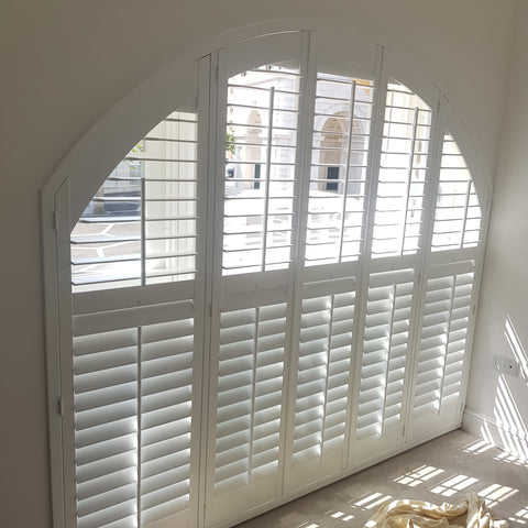 Arched shaped shutters in pure white installed in poundbury dorset