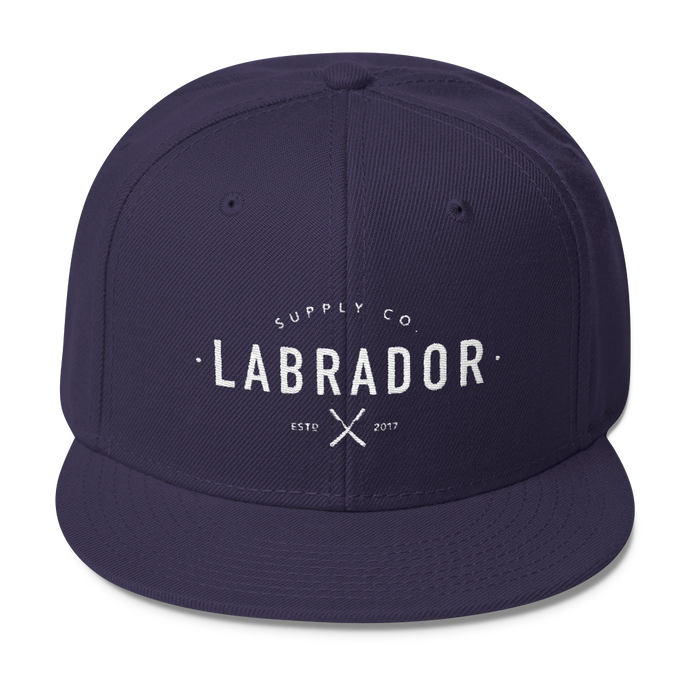 Snapback hat in NAVY BLUE with white Labrador Supply Co. logo stitched on front.