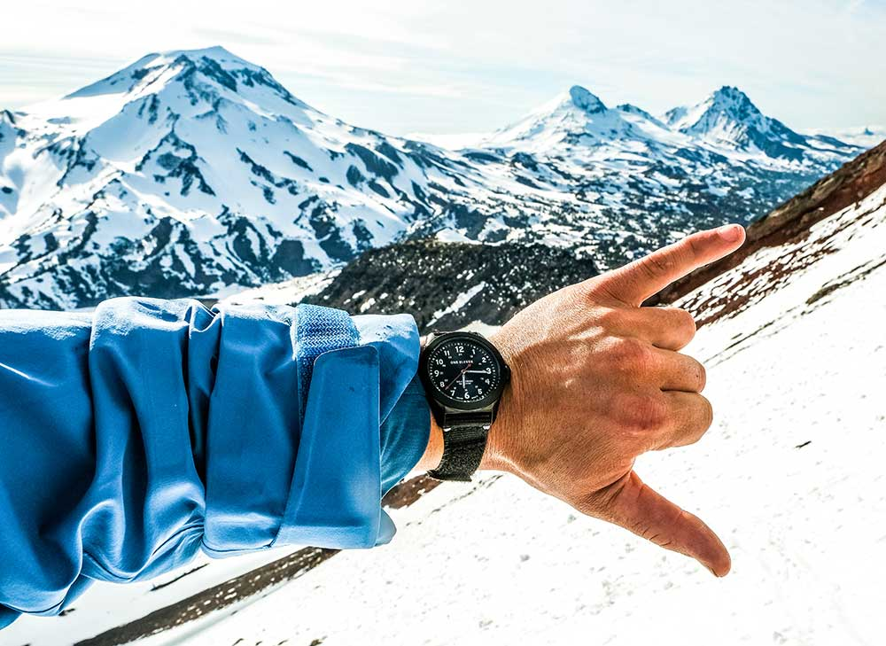 Black Field Watch on wrist at in front of the Three Sisters Volcanos