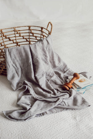 the grey coloured wrap is delicately draped over the cane basket.