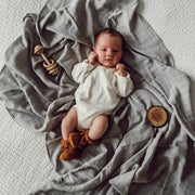 A baby lies on top of the stormy grey coloured wrap which is 100% organic cotton.