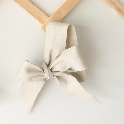 A natural linen coloured bow headband