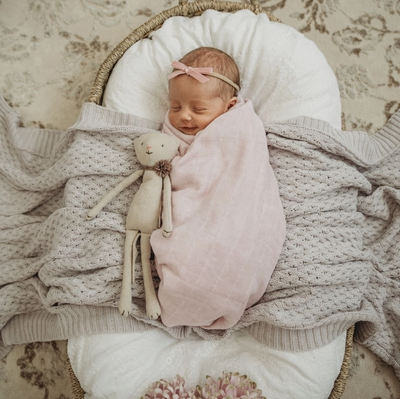 Baby girl wrapped up in a powder pink 100% organic wrap with a matching pink bow.