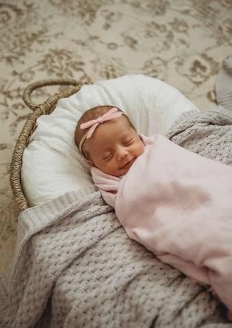 little baby girl asleep in a moses basket wrapped in a powder pink 100% organic cotton wrap.