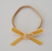 Soft velvet bow headband in gold with a soft nylon elastic band.