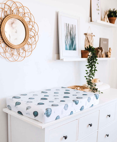 A nursery room with white walls, on the wall is a cane mirror and some art besides the art is a string of pearls plant cascading down to a change table. On top of the change table is a watercolour print cloud in 100% organic cotton by snuggle hunny.