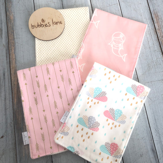 Gold dots, pink mermaid, pink/gold arrows, clouds burp cloths