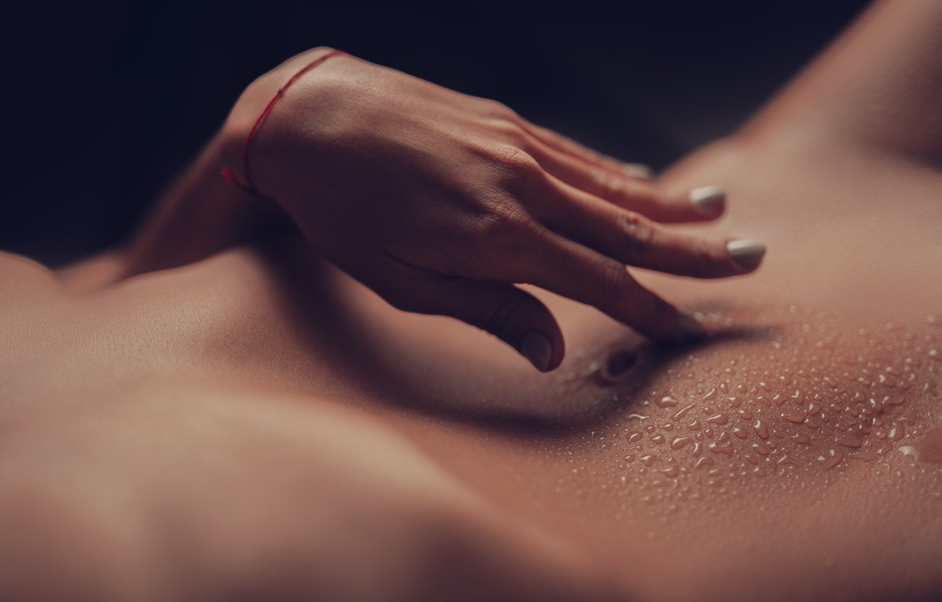 Crop naked woman touching her belly button