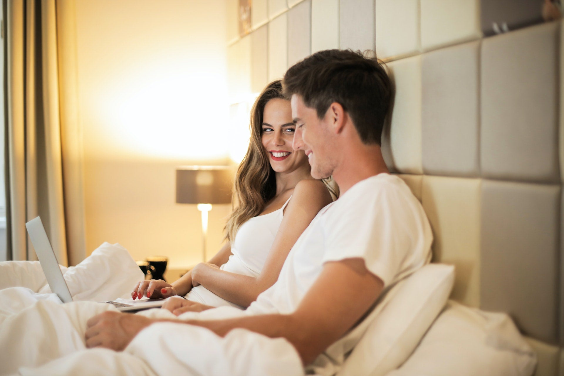 Smiling young couple watching porn together
