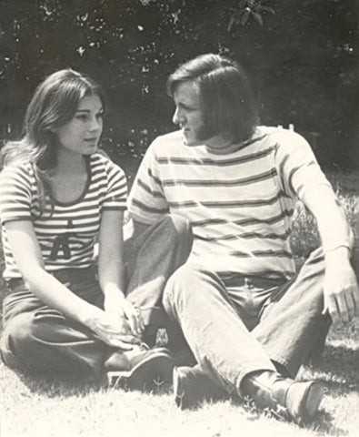 Couple sitting outside on grass.