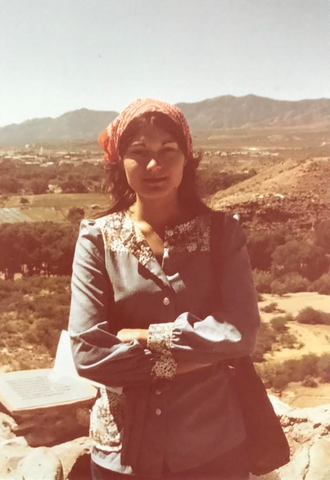 Woman standing outside wearing handkerchief and peasant blouse.