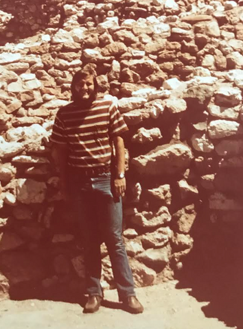 Man standing against a rock wall wearing t-shirt and jeans.