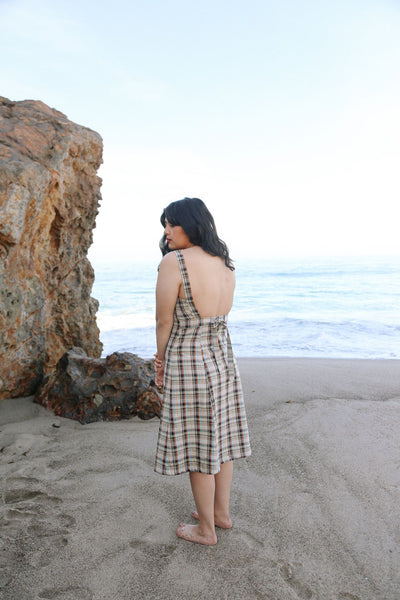 Woman standing on beach in sand wearing a navy plaid midi length dress. Her back is to the camera.