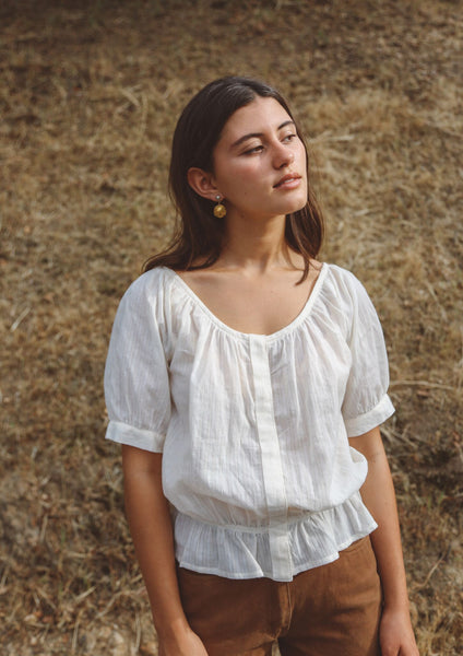 Woman wearing cream stripe peasant blouse outside.