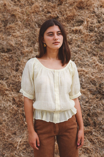 Woman wearing light yellow peasant blouse outside
