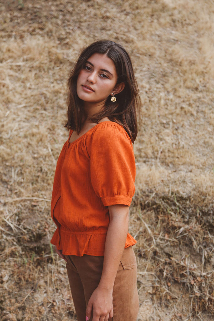 Woman wearing rust peasant blouse outside