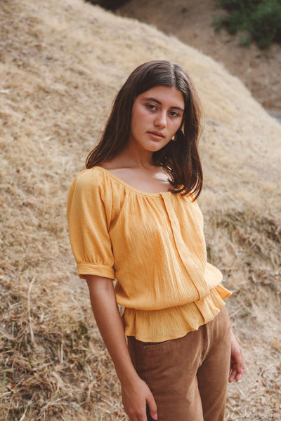 Woman wearing dark yellow peasant blouse outside