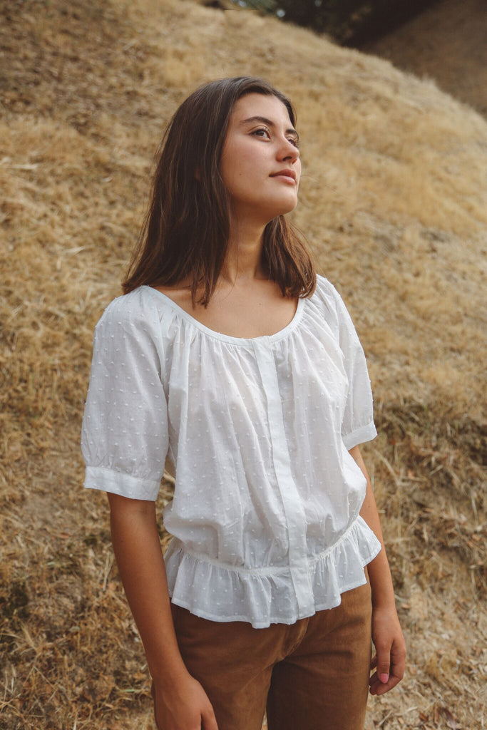 Woman wearing white dotted peasant blouse