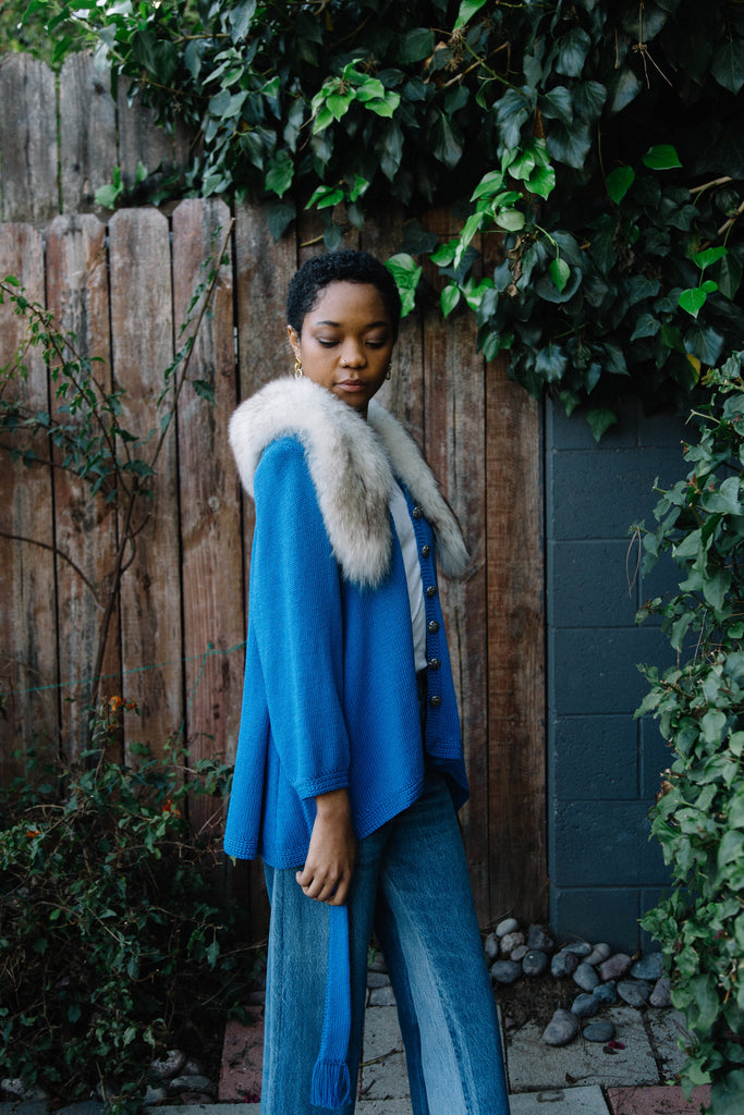 Woman standing side view wearing 1960s blue fur cardigan.