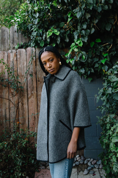 Woman wearing gray wool cape.