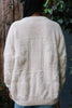 Back view of woman wearing oversized cream cardigan with alpaca pattern.