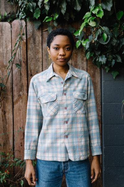 Woman wearing pastel plaid long sleeve shirt.