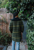 Back view of woman wearing moss green patterned coat.