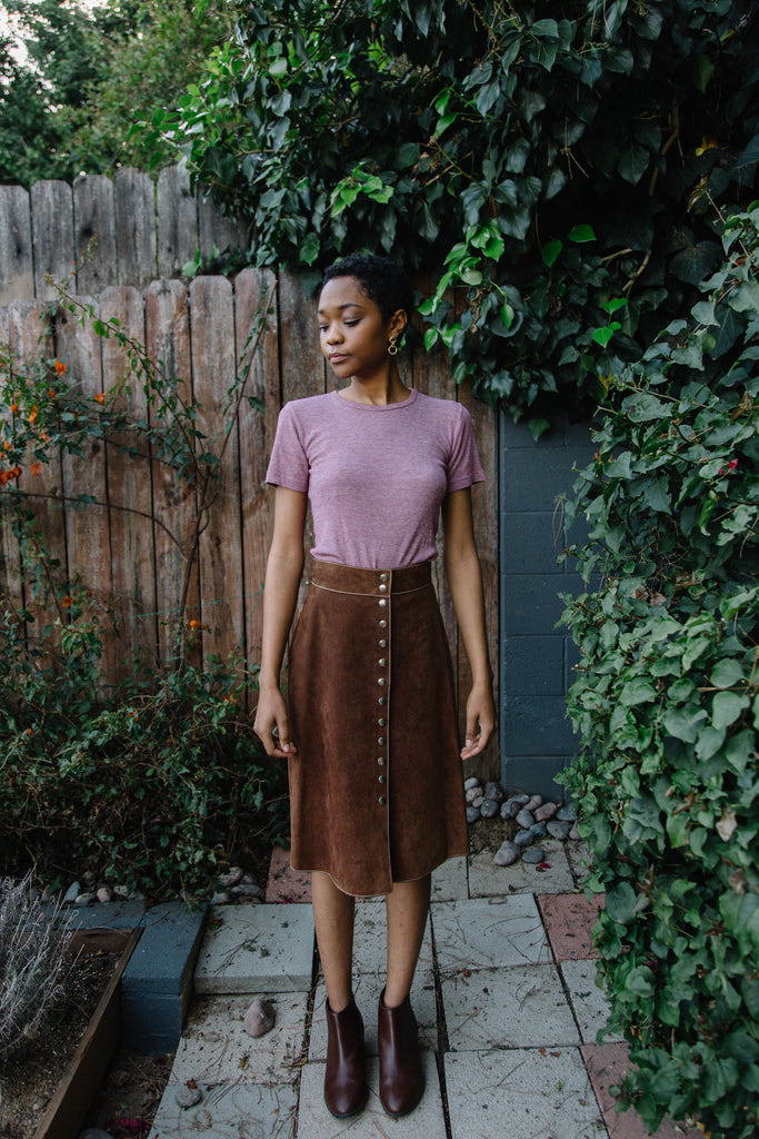Woman wearing brown suede knee length skirt.