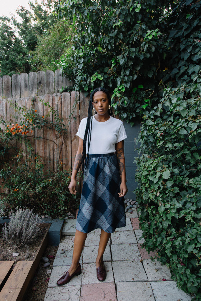 Woman wearing blue plaid wool midi skirt.