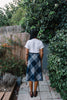 Back view of woman wearing blue plaid wool midi skirt.